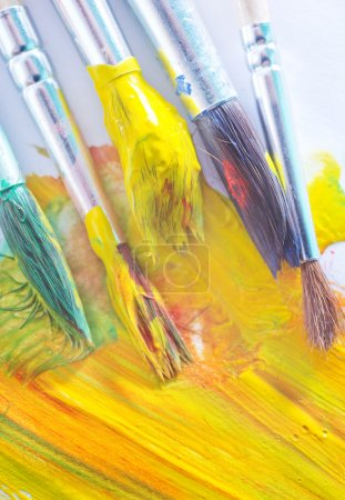 Brushes in yellow paint