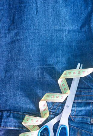 Jeans and green measuring tape