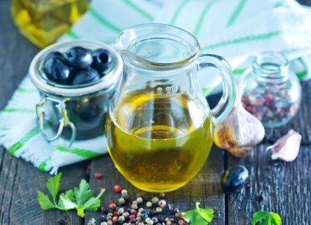 Photo pour Huile d'olive et olives noires sur la table en bois - image libre de droit