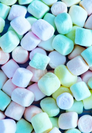 Color marshmallows on the wooden table