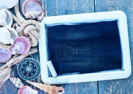 Photo pour Fond, coquillages et boussole sur une table - image libre de droit