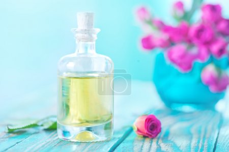 Photo for Rose oil in glass bottle and on a table - Royalty Free Image
