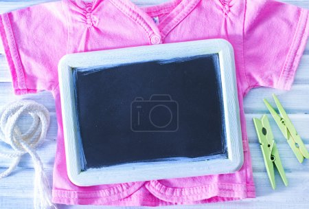 Baby clothes and black board