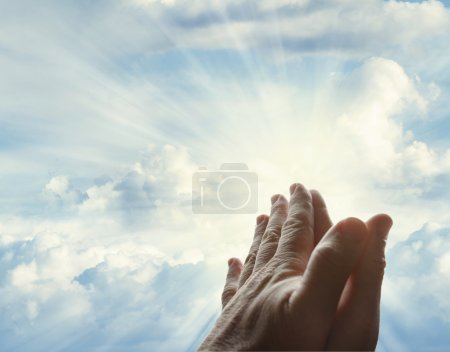 Prayer hands in sky