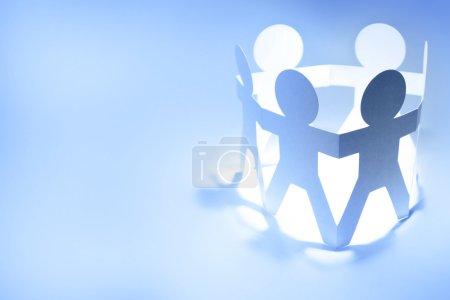 Photo pour Équipe de poupées en papier personnes tenant la main - image libre de droit