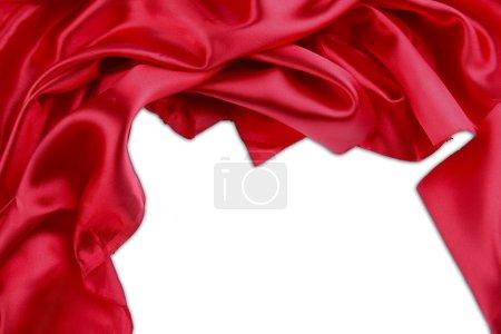 Photo pour Gros plan de plis en tissu de soie rouge sur fond uni. Espace de copie - image libre de droit