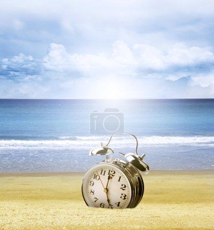 Photo pour Horloge coincée dans le sable à la plage. ciel lumineux derrière - image libre de droit