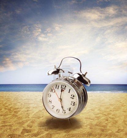 Photo pour Horloge sur le sable à la plage. ciel lumineux derrière - image libre de droit