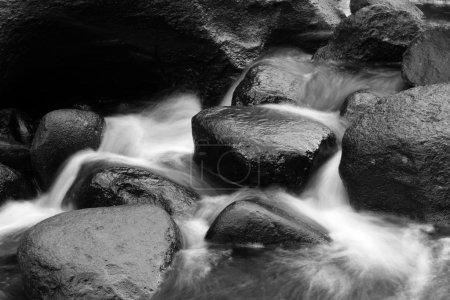 Photo pour Eau qui coule sur les rochers dans le ruisseau - image libre de droit