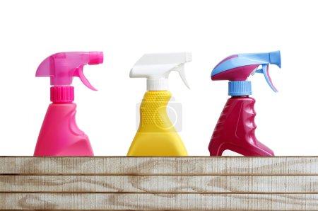 Photo pour Trois bouteilles de nettoyage au-dessus du bois - image libre de droit