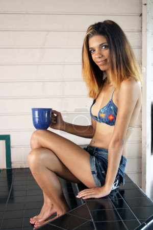Photo pour Un gros plan d'une charmante jeune fille hispanique avec un sourire lumineux et chaleureux, tenant une tasse de café - image libre de droit