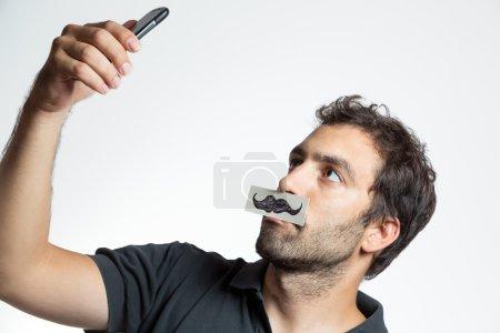 casual man make selfie portrait with fake moustache
