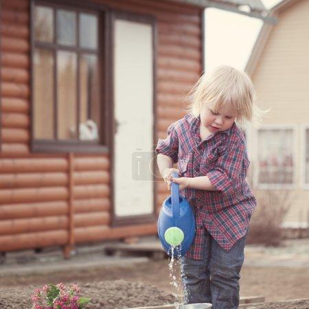 Photo pour Petite fille plantation et arrosage de fleurs dans le jardin sur fond de maison en bois - image libre de droit