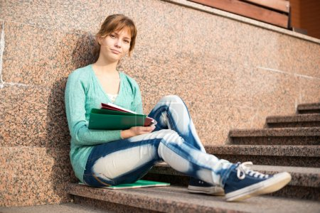 Photo for Portrait of a beautiful teenage student girl sitting on stairs in park with copy book and studing. Sunny summer day. Modern and casual lifestyle. Woman with note pad. - Royalty Free Image