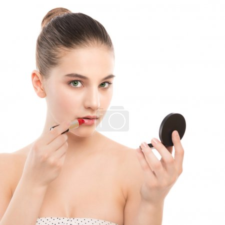 Photo for Portrait of beautiful young brunette woman with clean face. Beauty spa model girl with perfect fresh clean skin applying lipstick and use mirror. Youth and skin care concept. Isolated on a white - Royalty Free Image