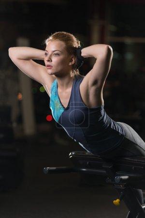 Photo pour Femme faisant des exercices pour les muscles abdominaux au gymnase de sport en salle. Fille faire du yoga s'étend après la course. Modèle Fitness au club de sport noir. - image libre de droit
