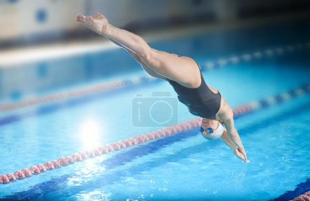 Photo for Portrait of a female swimmer, that jumping and diving into indoor sport swimming pool. Sporty woman. - Royalty Free Image