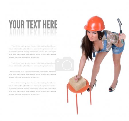 Photo for Young emotional woman dressed in jeans and orange helmet hammer in nail in wood piece. Isolated on white. - Royalty Free Image