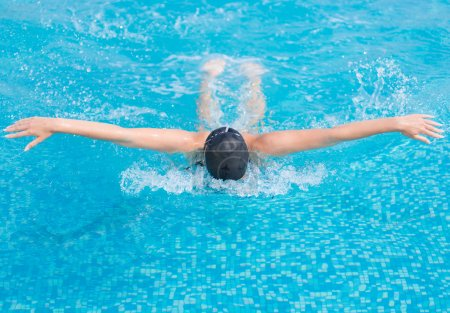 Photo for Young girl in goggles and cap swimming butterfly stroke style in the blue water pool - Royalty Free Image