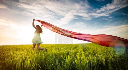 Photo pour Jeune femme courant avec des tissus dans un champ vert. Belle femme heureuse marchant dans la prairie rurale d'été. Belle fille bronzée. Sexy mince modèle caucasien ethnicité à l'extérieur - image libre de droit