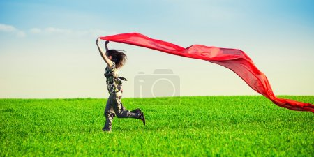 Photo for Beautiful young woman jumping on a green meadow with a colored red tissue. Happy female in wheat field with fabric. Summer picnic and freedom concept - Royalty Free Image