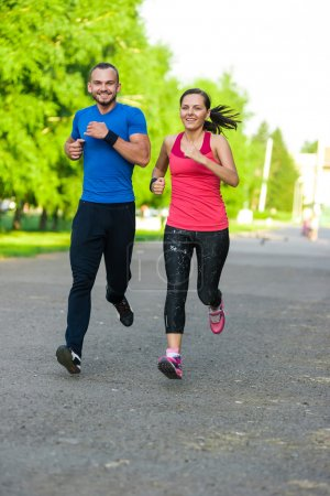 Photo for Runners training outdoors working out. City running couple jogging outside. City sport training in green park - Royalty Free Image