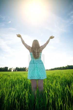 Photo for Happiness woman stay outdoor under sunlight of sunset. With raised hands at the sunrise time - Royalty Free Image