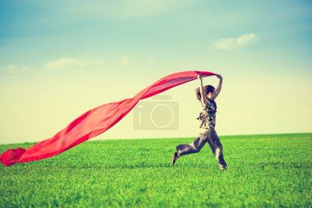 Photo pour Belle jeune femme sautant sur une prairie verte avec un tissu rouge coloré. Bonne femelle dans le champ de blé avec du tissu. Pique-nique d'été et concept de liberté - image libre de droit