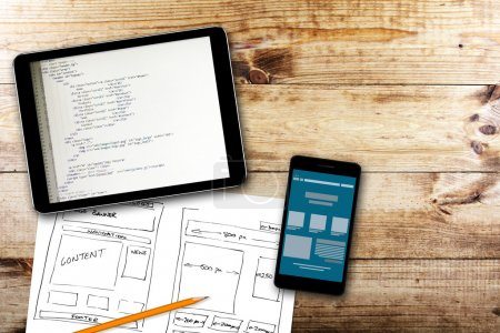 Photo for Website wireframe sketch and programming code on digital tablet - Royalty Free Image