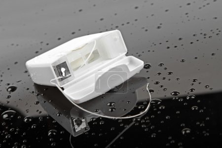 Photo pour Fil dentaire sur surface humide noire - image libre de droit