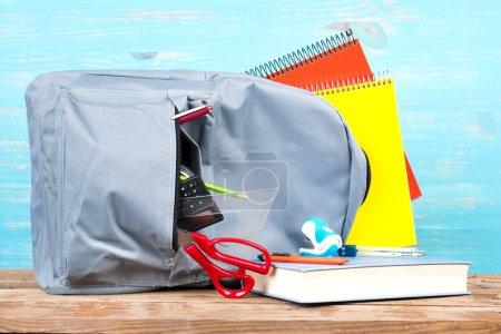 Photo pour Sac à dos avec outils scolaires sur fond turquoise - image libre de droit