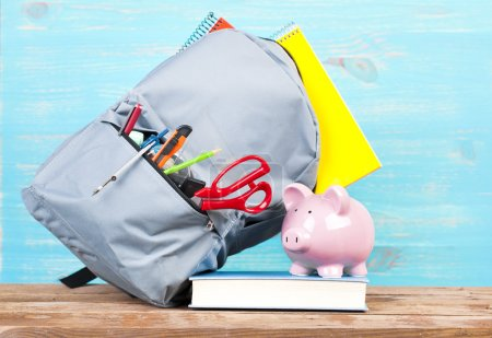 Backpack with school tools and piggy bank