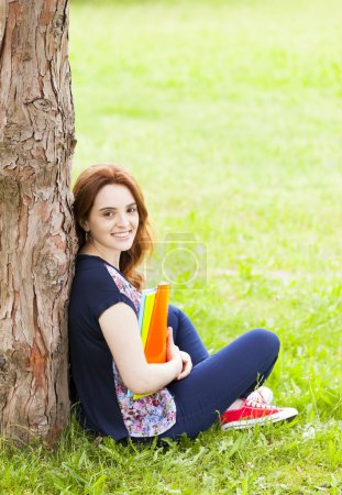 student girl sitting on the grass with notebooks