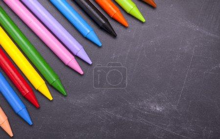 Crayons over chalkboard