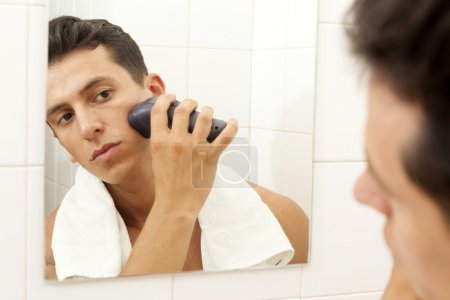Young man shaving with electric shaver at the bathroom