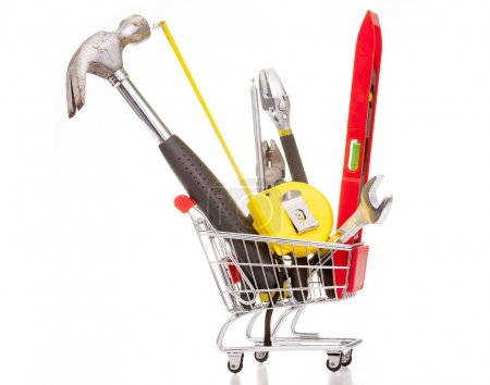 Photo for Shopping cart full of construction tools, isolated on white background - Royalty Free Image