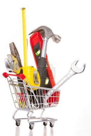 Foto de Carro de compras lleno de herramientas de construcción, aislado sobre fondo blanco - Imagen libre de derechos