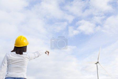 Photo pour Ingénieur femelle pointant vers les éoliennes - image libre de droit