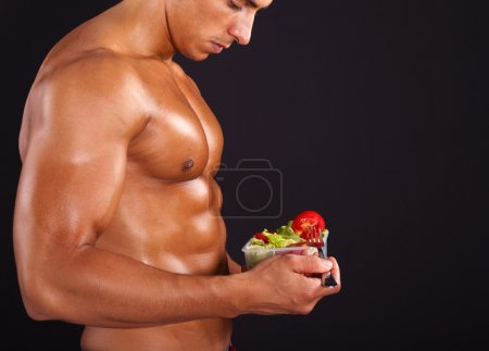 Photo for Fit man holding a bowl of fresh salad on black background - Royalty Free Image