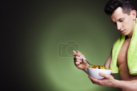 Photo for Young fitness man holding a bowl of fresh salad on dark background - Royalty Free Image
