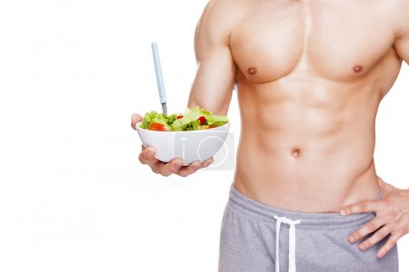 Photo for Muscular man holding a bowl of salad, isolated on white background - Royalty Free Image