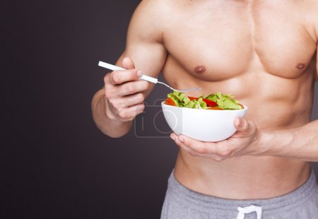 Man holding a bowl of fresh salad