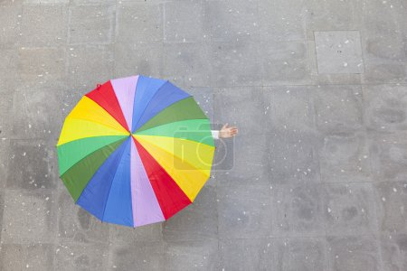 Woman hidden under multicolor umbrella