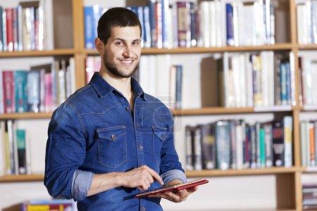 Photo pour Étudiant souriant tenant une tablette à la bibliothèque - image libre de droit