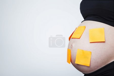Photo for Pregnant woman with post it on her belly against grey background - Royalty Free Image
