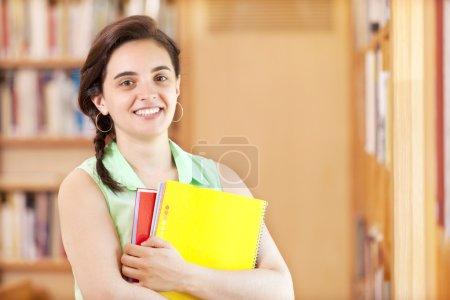 estudiante de pie con cuadernos en la biblioteca
