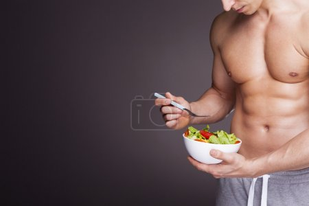 Photo for Athletic man holding a bowl of fresh salad on grey background - Royalty Free Image