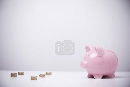 Photo for Piggybank and coins on grey background - Royalty Free Image