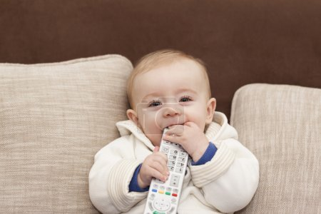 Smiling baby holding a remote control tv