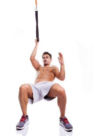 Fit man exercising suspension training on trx